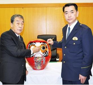 だるまに目を入れる中村会長(左)と春田署長
