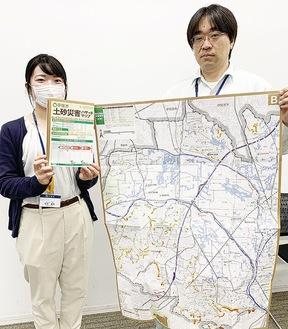 改訂版のマップを手にする市災害対策課職員