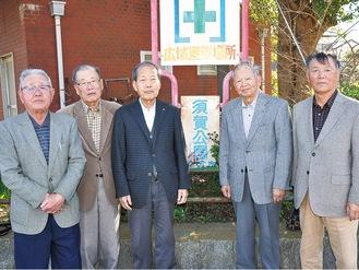 「須賀公園」の看板前に立つ須賀史談会のメンバーら