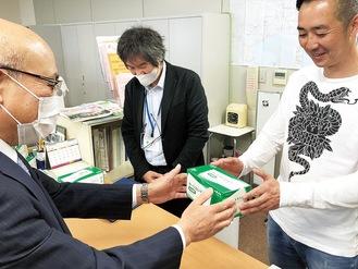 市医師会の事務局でマスクを受け取る医療関係者(右)