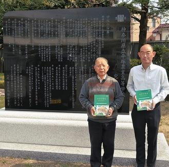 記念碑の前で記念誌を持つ陶山会長(左)と佐藤事務局長