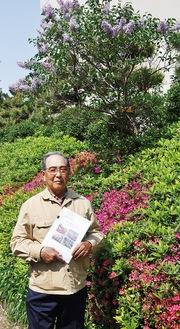 色づいた植栽を背に笑顔の高見澤理事長