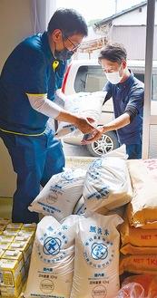市から提供された給食用の米の一部を倉庫に搬入するようす