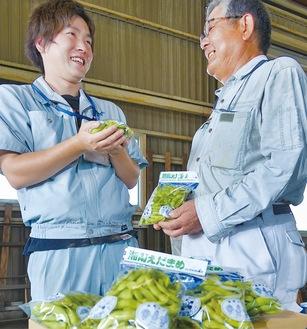 出荷前の枝豆を手にする生産者の松井さん(右)