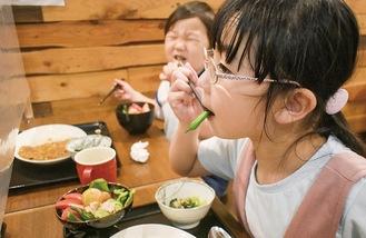 食堂でカレーを食べる姉弟