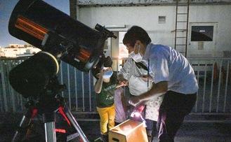 学芸員と一緒に望遠鏡をのぞく親子