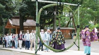 新設された茅の輪をくぐる宅野宮司や神社関係者