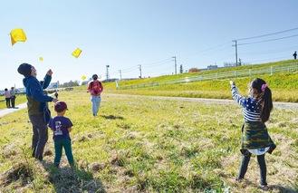 風向きを読み手作りの凧を飛ばす参加者ら