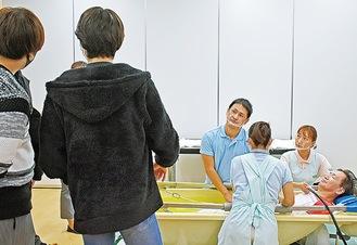 訪問入浴を見守る生徒ら(左)