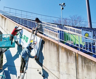 観客席横に横断幕を貼り付ける作業員ら(1月29日)