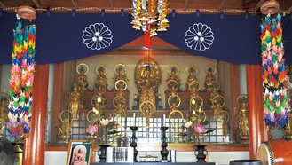 ガラスの向こうに三十三体の観音像が並ぶ。最上段中央が子易観世音菩薩