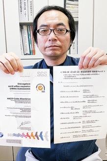 審査登録証(左)と関連の書類を手にする米山さん