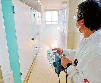 除菌ミストを散布するスタッフ