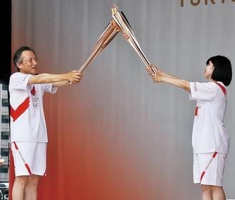トーチキスを行う武内さん(左)