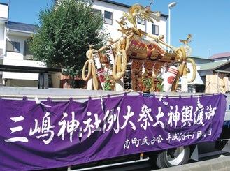 晴天の下、トラックに積載された大神輿が巡行した