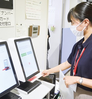 職員が案内状を受け取り、バーコードを機器で読み取る
