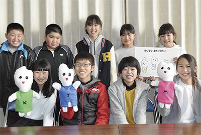 人形を手に笑顔をみせる運営委員会の児童ら