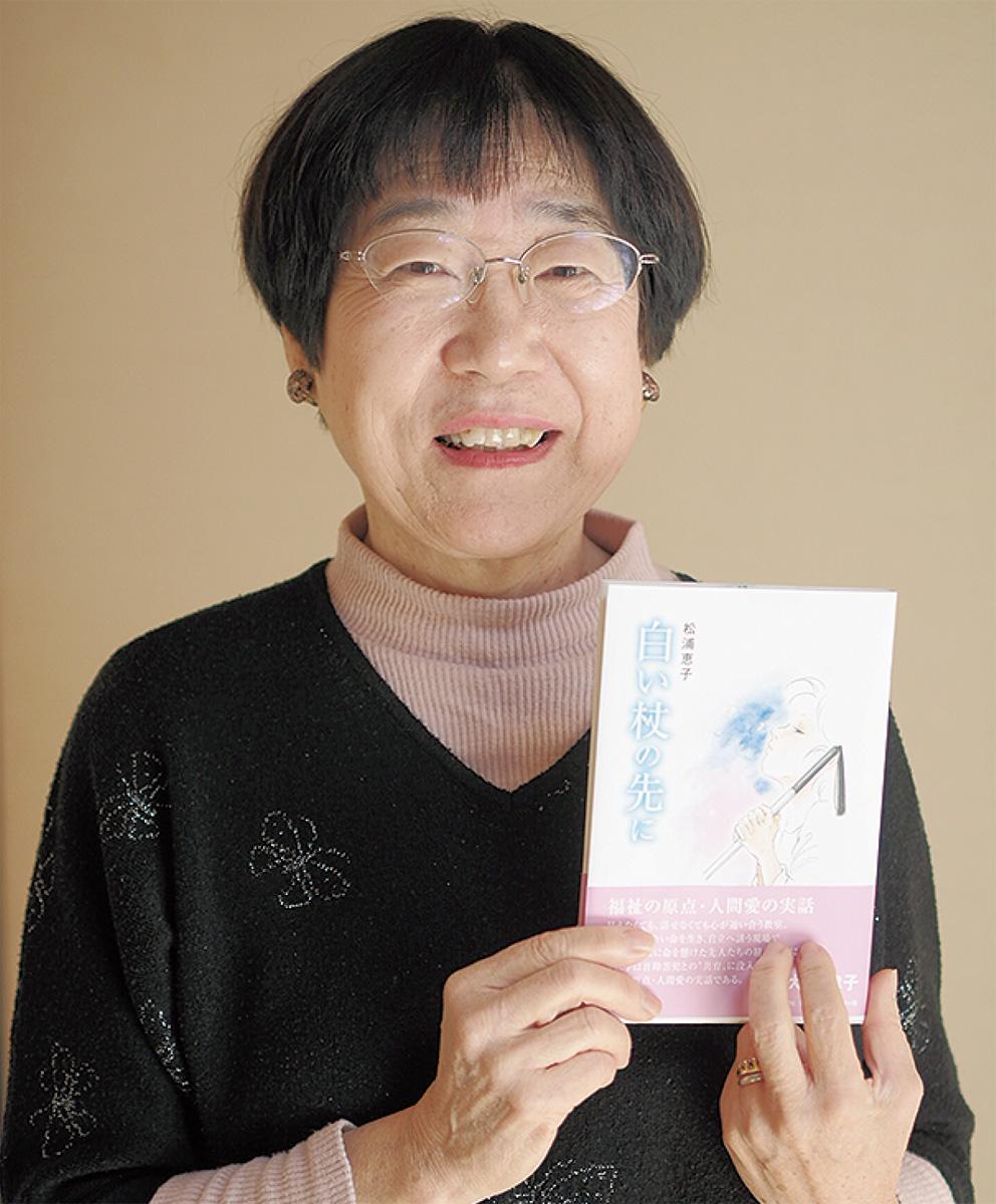 出版された本を持つ松浦さん