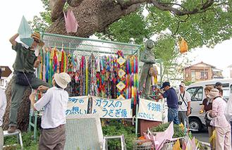 折鶴を飾り付ける町民たち