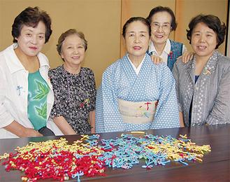 飾り結びを用いたトンボのブローチを作製した田中初枝さん(写真中央)と教室の生徒たち