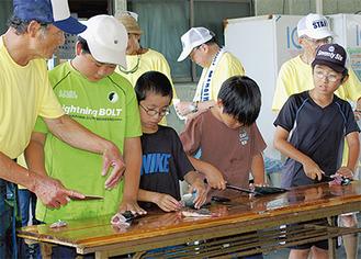 アウトリガーカヌーと漁業体験コースで、魚のさばき方を教わる子どもたち。「大名おろし」に挑戦した(大磯港内)