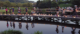 温かな光を放つ、手作りのランタンが木道に並べられた厳島湿生公園