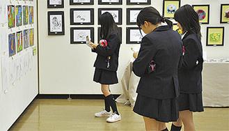 中学美術展の取材をする同校の女生徒たち