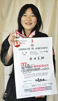 世界大会の優勝メダルと賞状を手にする安田さん