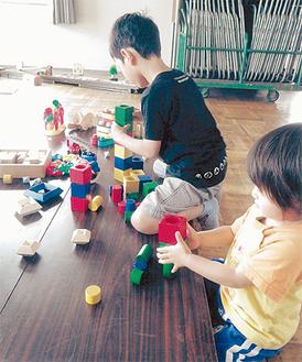 木のブロックを積み上げて遊ぶ子ども(写真提供/工房トイ・パレット)