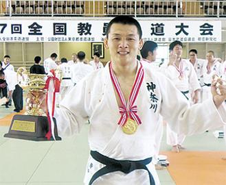 優勝杯を手にする田中教諭