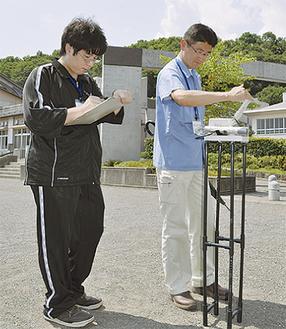 職員が読み上げる放射線量を記録する井上さん(写真左)