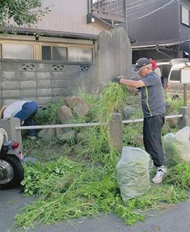 移街碑の周囲で草取りに汗を流すボランティアの住民たち