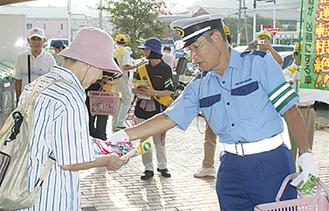 買い物客へ啓発物を配る交通指導員