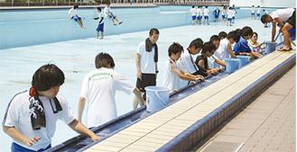 プール清掃に汗を流す生徒たち