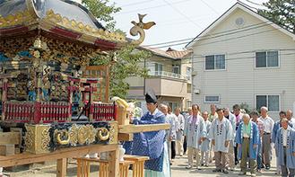 修繕される神輿の前で安全を祈願する参列者たち