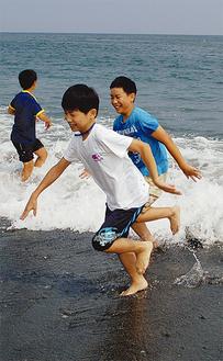 梅沢海岸で水遊びを楽しむ児童
