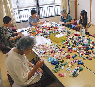 届けられた鶴を一つひとつ糸に通す手作業の準備は7月下旬まで行われた