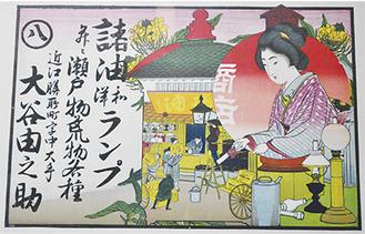 油や和洋ランプ、瀬戸物などを扱う商店の引き札。石版と木版の技法で作られたという。写真右下は江戸時代の行灯と秋澤館長