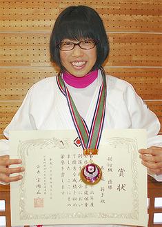 賞状とメダルを手に笑顔