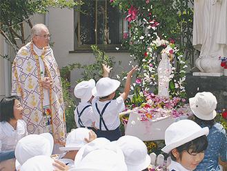 マリア像に花びらをかけ祝福した