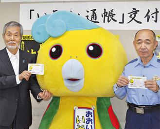 通帳を手にする中崎久雄大磯町長(左)と加藤登志夫大磯警察署長