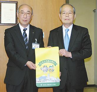 カバーを贈った筒井会長(右)