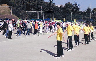 準備運動の体操をする参加者