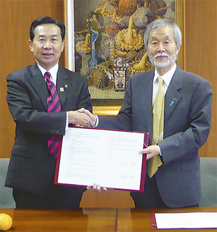 調印式を終えた中崎町長(右)と谷ケ崎市長