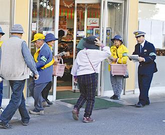 買い物客にチラシを配る関係者
