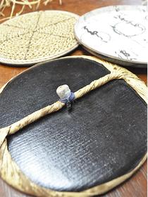 ばれん(手前)を構成する渦巻き状の芯(左奥)と小皿のような形状の当て皮(右奥)。当て皮の表面には漆を幾重にも塗り込む