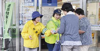 啓発物を配る交通安全母の会の会員(二宮町)