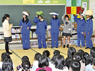 特産品の被り物をして劇を行う生徒