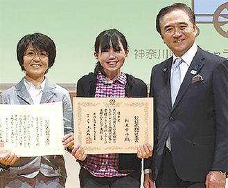 黒岩知事(右)から表彰を受けた松本さん(中央)