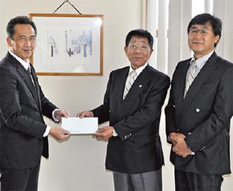 寄付金を手渡す善波会長(中央)